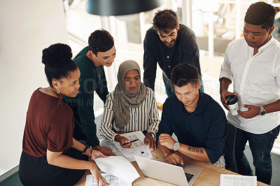 Buy stock photo Cropped shot of a group of young business colleagues gathered around a laptop in their office