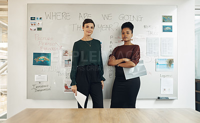 Buy stock photo Cropped portrait of two attractive young businesswomen standing in front of a whiteboard in their office boardroom