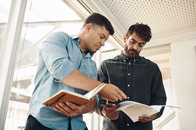 Buy stock photo Cropped shot of two handsome young businessmen looking over their notes after a successful meeting in the boardroom