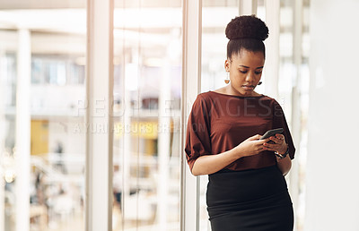 Buy stock photo Cropped shot of an attractive young businesswoman using her cellphone while standing in the office