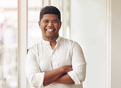 Buy stock photo Cropped portrait of a handsome young businessman standing with his arms crossed in the office