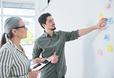 Buy stock photo Shot of two businesspeople brainstorming with notes on a wall in an office