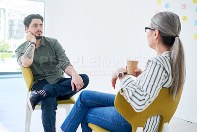Buy stock photo Shot of two businesspeople having a discussion while sitting on chairs in an office