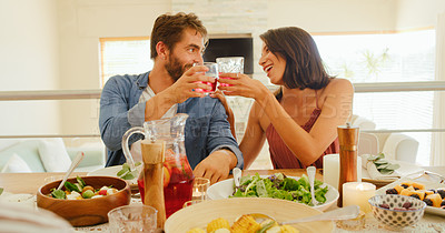 Buy stock photo Shot of a young man and woman toasting with drinks during a lunch party at home