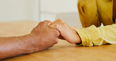 Buy stock photo Cropped shot of an unidentifiable man and woman sitting at a table and holding hands