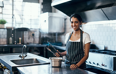 Buy stock photo Portrait of a confident young woman standing in the kitchen of her cafe