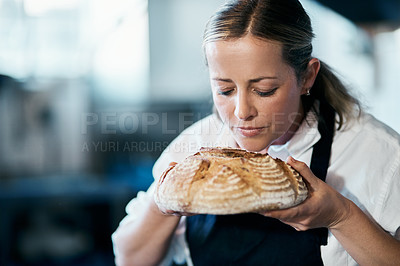 Buy stock photo Shot of a mature woman smelling a freshly baked loaf of bread in her cafe