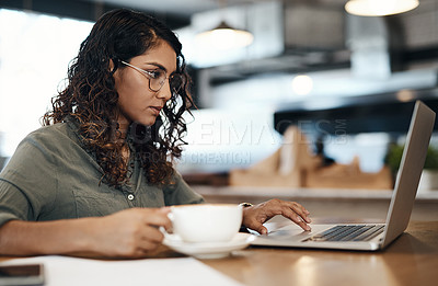 Buy stock photo Shot of a young woman using a laptop and having coffee in a cafe