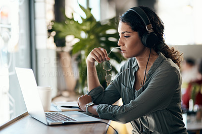 Buy stock photo Shot of a young woman using a laptop and headphones in a cafe