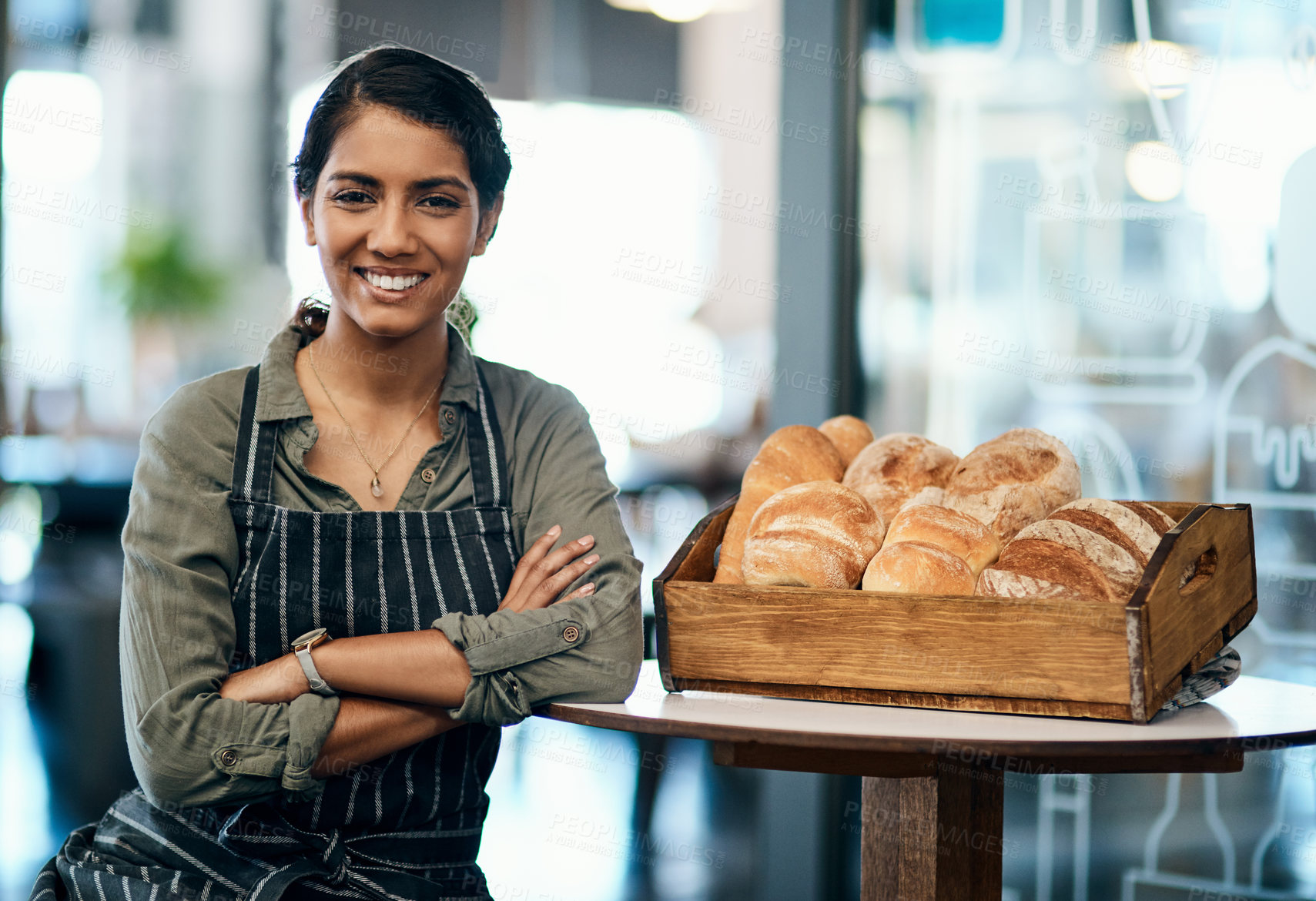 Buy stock photo Shot of a young woman serving a selection of freshly baked breads in her bakery