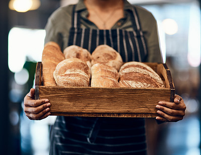 Buy stock photo Cropped shot of a woman holding a selection of freshly baked breads in her bakery