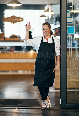Buy stock photo Shot of a mature woman standing at the entrance of her cafe and waving