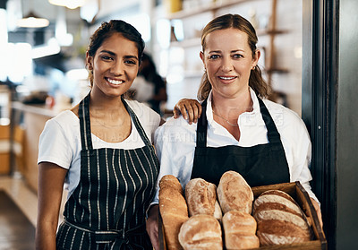 Buy stock photo Shot of two women holding a selection of freshly baked breads in their bakery