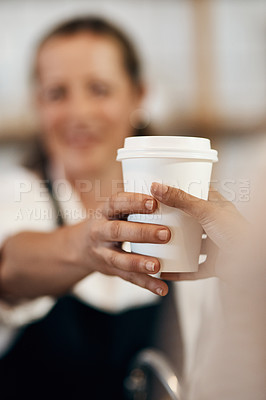 Buy stock photo Cropped shot of a barista handing a customer a cup of coffee at a cafe