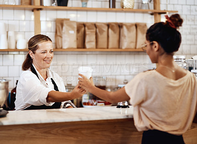Buy stock photo Shot of a mature barista handing a customer a cup of coffee at a cafe
