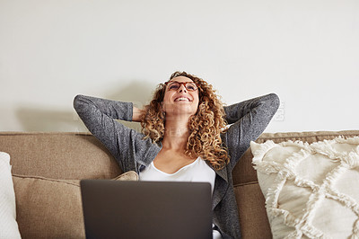 Buy stock photo Shot of a happy young woman using a laptop on the sofa at home