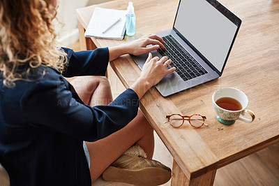 Buy stock photo Cropped shot of a woman using a laptop at a table while working from home