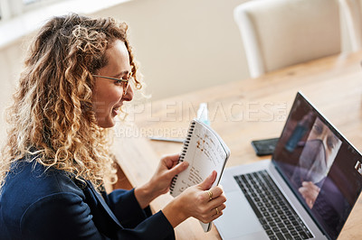 Buy stock photo Shot of a young woman using a laptop to make a video call while working from home