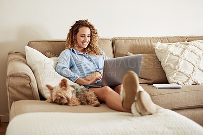 Buy stock photo Shot of a young woman using a laptop on the sofa while working at home