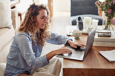 Buy stock photo Shot of a young woman using a laptop while working in the living room at home