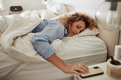 Buy stock photo Shot of a young woman waking up in bed and checking her smartphone