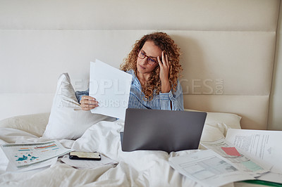 Buy stock photo Shot of a young woman using a laptop and looking stressed while working in bed