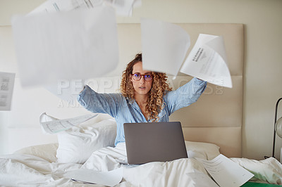 Buy stock photo Shot of a young woman using a laptop and throwing paperwork in the air while working in bed