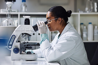 Buy stock photo Cropped shot of an attractive young female scientist working on a microscope in her laboratory