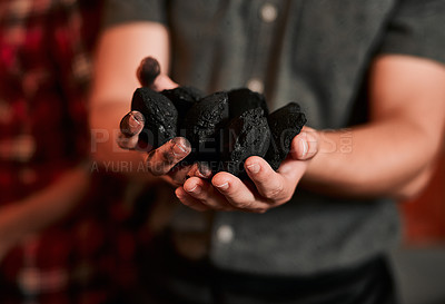 Buy stock photo Closeup shot of an unrecognisable man holding a pile of charcoal