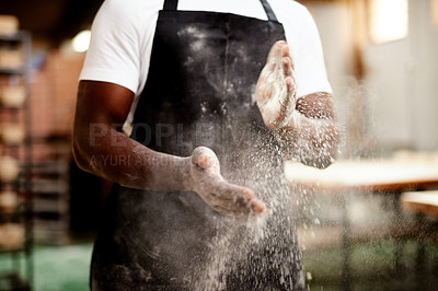 Buy stock photo Cropped shot of an unrecognizable male baker dusting the flour off his hands