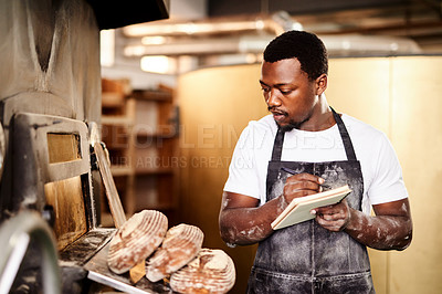Buy stock photo Cropped shot of a male baker making notes while working in his bakery