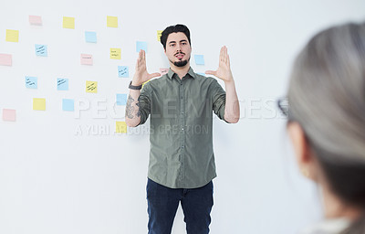 Buy stock photo Shot of a young businessman giving a presentation while standing against a wall with notes in an office