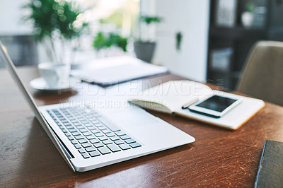 Buy stock photo Still life shot of a laptop, notebook and cellphone on a table in an office