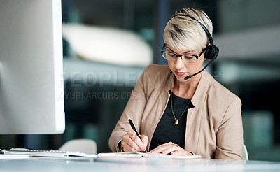 Buy stock photo Shot of a young businesswoman wearing a headset while writing notes in an office