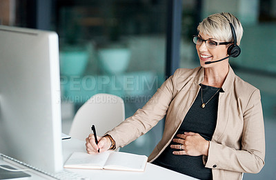 Buy stock photo Shot of a pregnant businesswoman wearing a headset while writing notes in an office