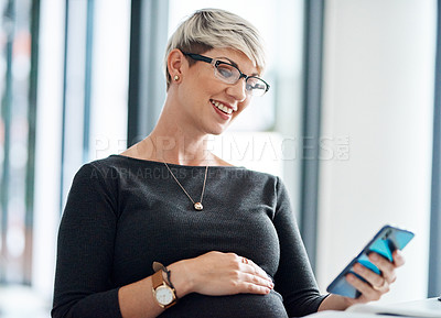 Buy stock photo Shot of a pregnant businesswoman using a cellphone in an office