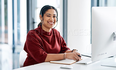 Buy stock photo Portrait of a young businesswoman wearing a headset while working on a computer in an office