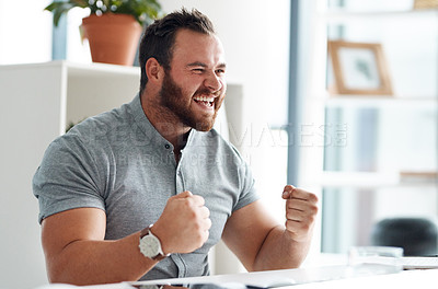 Buy stock photo Shot of a young businessman cheering while working on a computer in an office