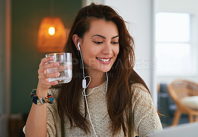 Buy stock photo Shot of an attractive young woman using a laptop and having water while working at home