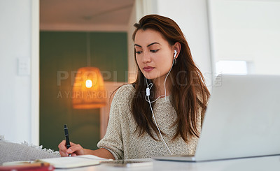 Buy stock photo Shot of an attractive young woman using a laptop and earphones at home