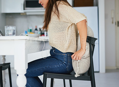 Buy stock photo Shot of a young woman adjusting a cushion and chair while working from home
