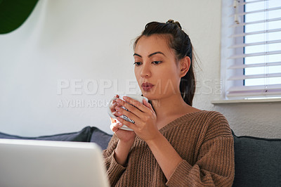 Buy stock photo Shot of an attractive young woman using a laptop and having coffee on the sofa at home