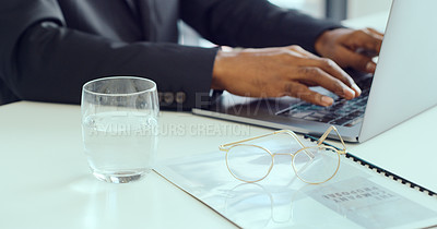 Buy stock photo Cropped shot of an unrecognisable businessman using a laptop at his desk in a modern office