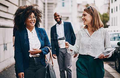 Buy stock photo Shot of two businesswomen having a discussion while walking through the city together