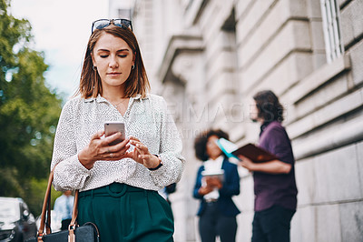 Buy stock photo Shot of a businesswoman using her cellphone while out in the city