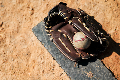Buy stock photo Shot of a baseball mitt and ball lying on the pitch during the day