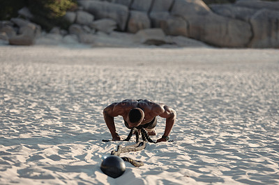 Buy stock photo Shot of a muscular young man doing pushups while exercising with battle ropes at the beach