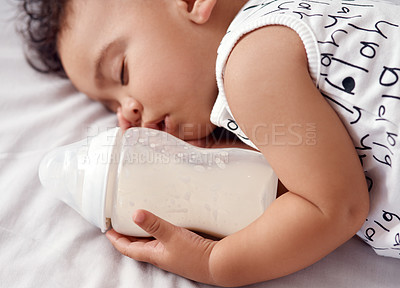 Buy stock photo Shot of an adorable baby boy sleeping with his bottle of milk on the bed at home