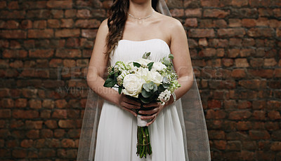 Buy stock photo Cropped shot of an unrecognisable woman holding a bouquet against a brick wall on her wedding day