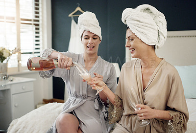 Buy stock photo Shot of a bride and her maid of honour having champagne while getting ready